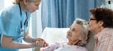 passionate nurse holding the hands of an old woman