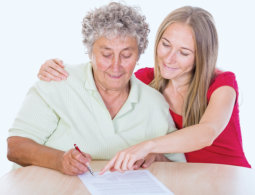 caregiver teaching an old woman to write