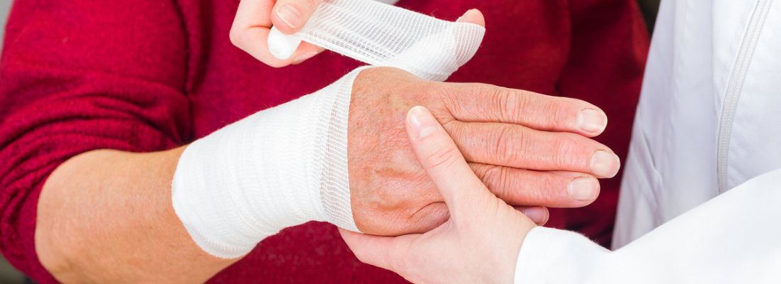 caregiver bandaging an old woman's wounds